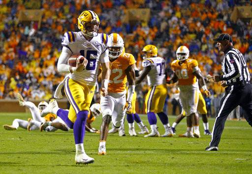 LSU quarterback Danny Etling (16) runs in for a touchdown as he's chased by Tennessee defensive back Micah Abernathy (22) during the first half of an NCAA college football game Saturday, Nov. 18, 2017, in Knoxville, Tenn. (AP Photo/Wade Payne)