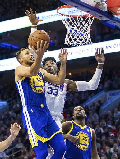 Golden State Warriors' Stephen Curry, left, goes up for the shot with Philadelphia 76ers' Robert Covington, right, defending during the first half of an NBA basketball game Saturday, Nov. 18, 2017, in Philadelphia. (AP Photo/Chris Szagola)
