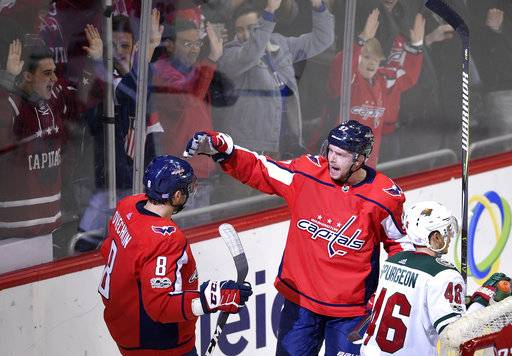 Washington Capitals center Evgeny Kuznetsov (92), of Russia, celebrates his goal with left wing Alex Ovechkin (8), also of Russia, as Minnesota Wild defenseman Jared Spurgeon (46) skates by during the third period of an NHL hockey game, Saturday, Nov. 18, 2017, in Washington. (AP Photo/Nick Wass)