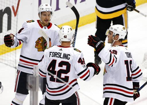 Chicago Blackhawks' Gustav Forsling (42) celebrates his goal with Jonathan Toews (19) and Richard Panik (14) during the first period of an NHL hockey game against the Pittsburgh Penguins in Pittsburgh, Saturday, Nov. 18, 2017. (AP Photo/Gene J. Puskar)