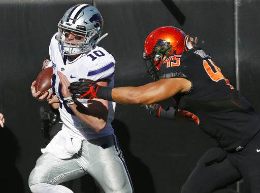 Kansas State quarterback Skylar Thompson (10) is pushed out of bounds by Oklahoma State linebacker Chad Whitener (45) in the first half of an NCAA college football game in Stillwater, Okla., Saturday, Nov. 18, 2017. (AP Photo/Sue Ogrocki)