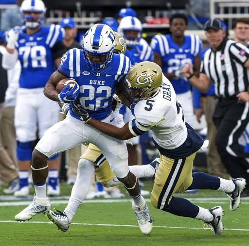 Duke's Brittain Brown (22) carries the ball as Georgia Tech's A.J. Gray (5) attempts a tackle during the first half of an NCAA college football game in Durham, N.C., Saturday, Nov. 18, 2017. (AP Photo/Ben McKeown)