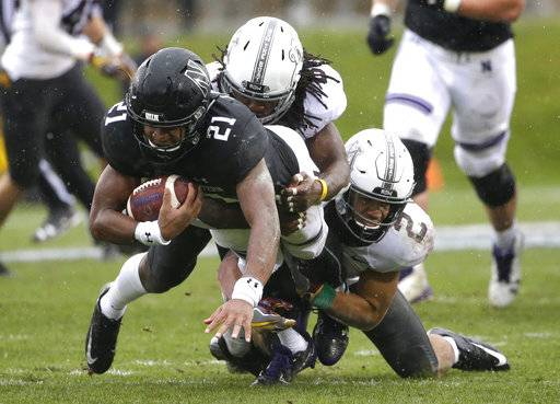 Northwestern running back Justin Jackson (21) is tackled by Minnesota defensive back Duke McGhee and defensive back Jacob Huff (2) during the first half of an NCAA college football game in Evanston, Ill., Saturday, Nov. 18, 2017. (AP Photo/Nam Y. Huh)