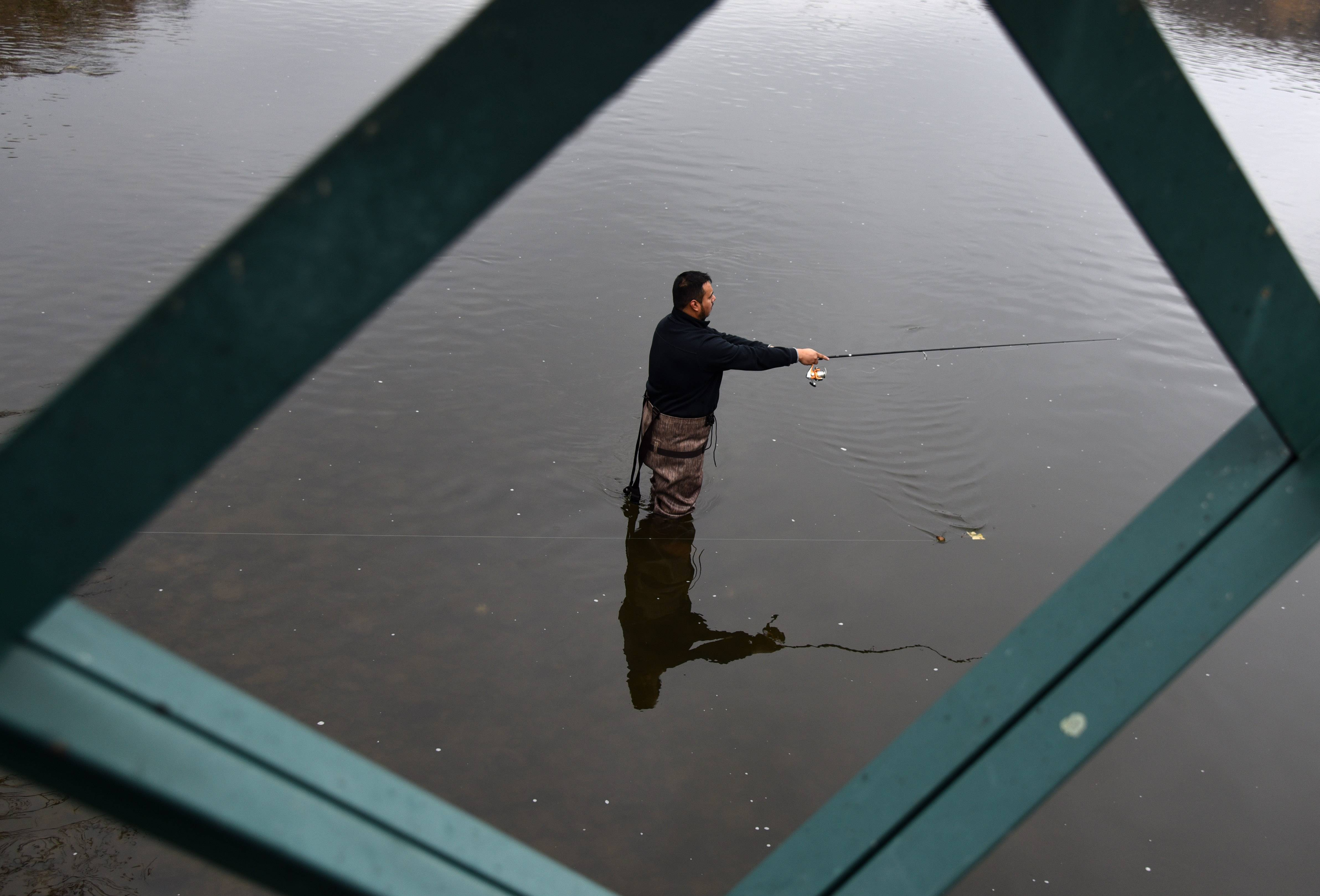 "Aldo Miranda, of Cicero fishes the waters of the Fox River near Fabyan Forest Preserve in Geneva Monday. Though he's fished there successfully several times before, up to this point he'd had no luck. ""I'm going to change up my gear, see if they're hungry for something else,"" he said."
