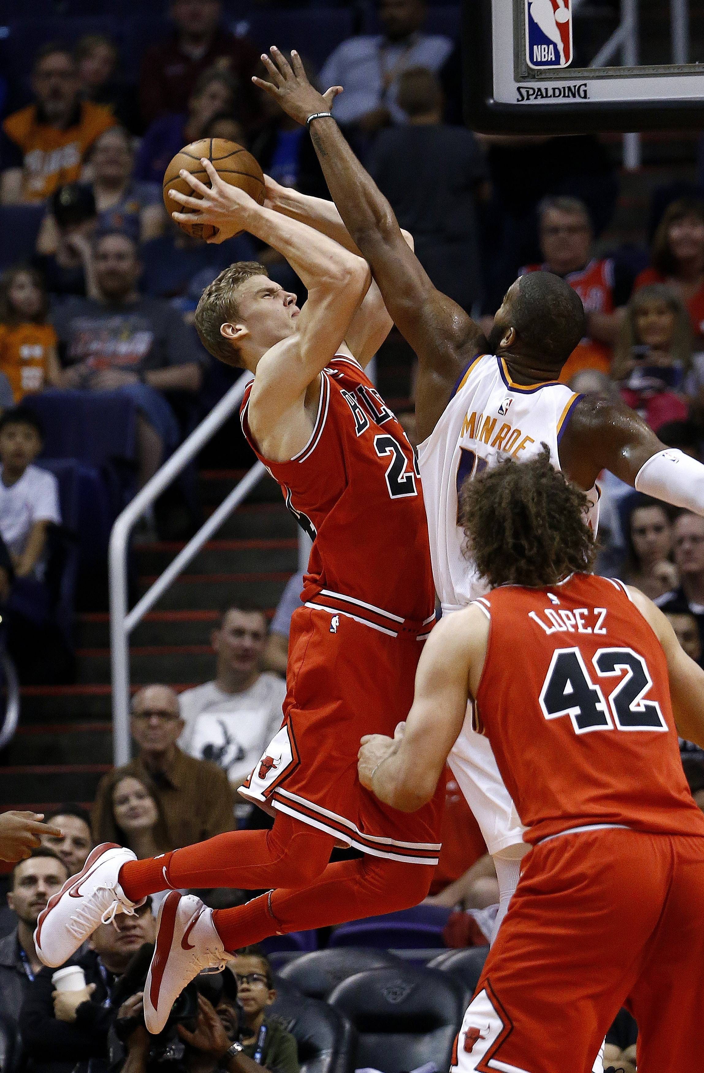 Chicago Bulls forward Lauri Markkanen, left, shoots as he is fouled by Phoenix Suns center Greg Monroe, back right, while Bulls' Robin Lopez (42) watches during the first half of an NBA basketball game Sunday, Nov. 19, 2017, in Phoenix. (AP Photo/Ross D. Franklin)