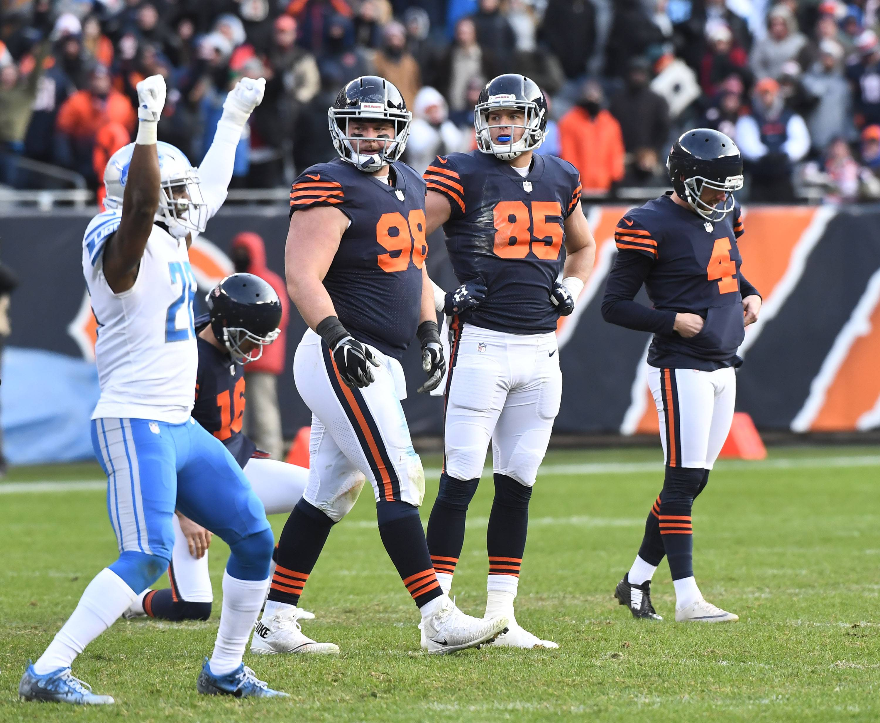 Chicago Bears kicker Connor Barth bows his head as teammates Chicago Bears Mitch Unrein and Daniel Brown watch Detroit Lions strong safety Don Carey celebrate the missed field goal with only seconds left in regulation Sunday at Soldier Field in Chicago.