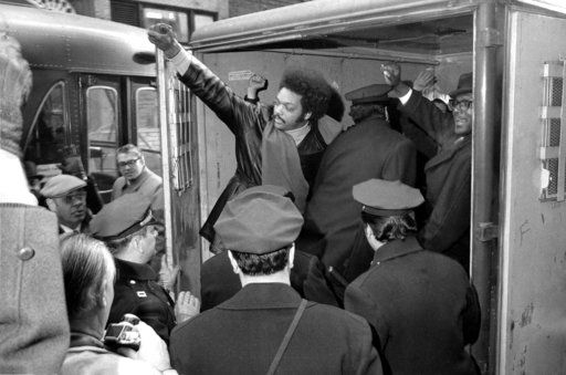 FILE - In this Feb. 2, 1971 file photo, Rev. Jesse Jackson raises a clenched fist from the back of a police van after he and 11 others from Operation Breadbasket were arrested during a sit-in at the Atlantic and Pacific Tea Co., offices in New York City. The organization, part of the Southern Christian Leadership Conference, has been protesting A&P's alleged discrimination against blacks.