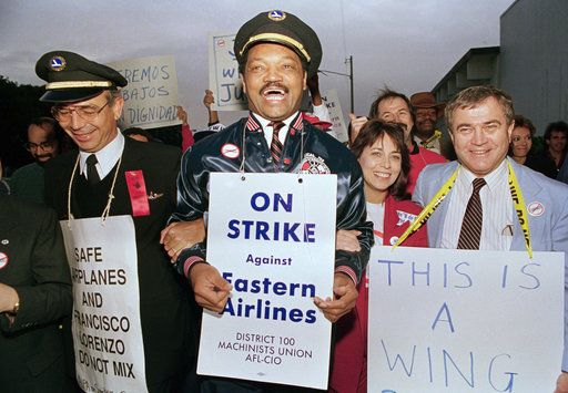 The Rev. Jesse Jackson, center, wearing a pilot's hat and a Machinists union jacket, walks the picket line in Miami on Wednesday, March 9, 1989, with Eastern Airlines Machinists Union District 100 President Charles Bryan, right, and an unidentified pilot, left. Jackson spoke to a Solidarity rally of about 1,000 machinists, pilots and flight attendants at the Machinists' union headquarters in Miami.