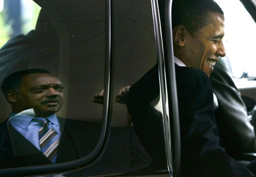 FILE - In this Monday, June 4, 2007 file photo, Democratic presidential hopeful Sen. Barack Obama, D-Ill., right, laughs after saying goodbye to Rev. Jesse Jackson, reflected left, after Obama addressed the Rainbow PUSH Coalition's annual conference breakfast in Rosemont, Ill.