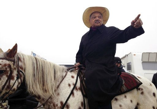 "FILE - In this Wednesday, Oct. 26, 2016 file photo, civil rights activist Jesse Jackson sits atop a horse while visiting the protest camp against the Dakota Access oil pipeline outside Cannon Ball, N.D. Jackson said he came ""to pray together, protest together and if necessary, go to jail together."""