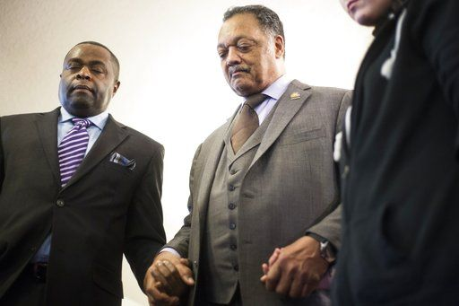 FILE - In this Sunday, Jan. 17, 2016 file photo, Rev. Jesse Jackson, center, holds hands with others at Heavenly Host Full Gospel Baptist Church in Flint, Mich. Jackson visited to address the controversy of lead contamination in the city's tap water. (Conor Ralph/The Flint Journal-MLive.com via AP)