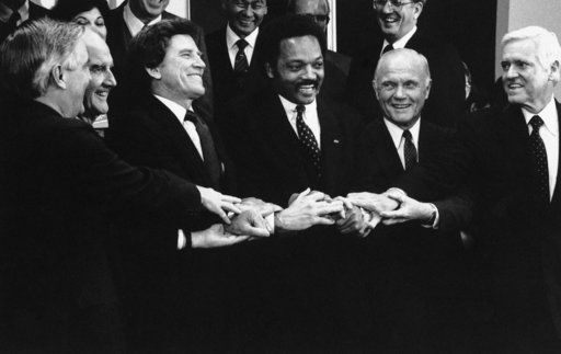 FILE - In this Tuesday, Dec. 7, 1983 file photo, six of the 1984 Democratic presidential candidates, from left, Walter Mondale, George McGovern, Sen. Gary Hart, Rev. Jesse Jackson, Sen. John Glenn and Sen. Ernest Hollings, join hands to conclude a five-city fundraising sweep, in Albuquerque, N.M. The candidates linked hands to show unity against the Reagan administrations policies.