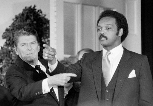 FILE - In this Jan. 4, 1984 file photo, President Ronald Reagan, left, and Democratic presidential hopeful Jesse Jackson, right, gesture shortly after a White House Rose Garden ceremony honoring Navy Lt. Robert O. Goodman. Jackson was instrumental in securing Goodman's release from Syria after a month in captivity.