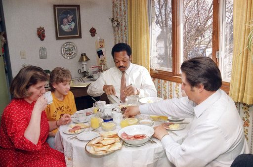 FILE - In this March 31, 1988 file photo, presidential candidate Jesse Jackson joins the Becker family for breakfast after spending the night in their home in Cudahy, Wis. Jackson is campaigning in the state for the April 5 primary.