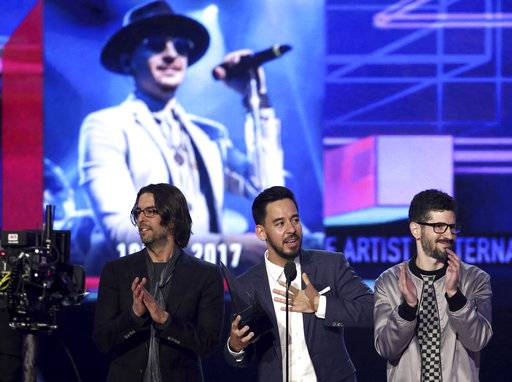 Rob Bourdon, from left, Mike Shinoda, and Brad Delson of Linkin Park accept the award for favorite artist alternative rock at the American Music Awards at the Microsoft Theater on Sunday, Nov. 19, 2017, in Los Angeles. Pictured on screen is late member Chester Bennington. (Photo by Matt Sayles/Invision/AP)