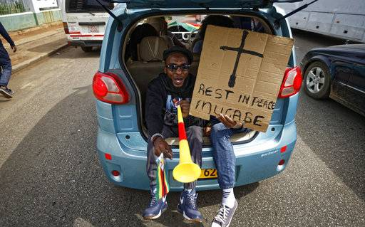 "Protesters demanding President Robert Mugabe stand down ride in the back of a car with a placard ""Rest in peace Mugabe"" as they drive towards State House in Harare, Zimbabwe Saturday, Nov. 18, 2017. In a euphoric gathering that just days ago would have drawn a police crackdown, crowds marched through Zimbabwe's capital on Saturday to demand the departure of President Robert Mugabe, one of Africa's last remaining liberation leaders, after nearly four decades in power."