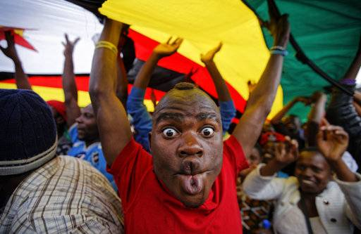 A happy protester pulls a face as he and others stand under a large national flag, at a demonstration of tens of thousands at Zimbabwe Grounds in Harare, Zimbabwe Saturday, Nov. 18, 2017. Opponents of Mugabe are demonstrating for the ouster of the 93-year-old leader who is virtually powerless and deserted by most of his allies.