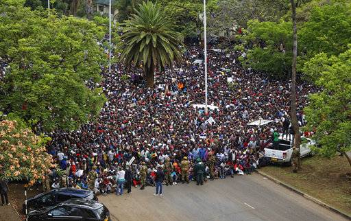 A crowd of thousands of protesters demanding President Robert Mugabe stand down gather in front of an army cordon on the road leading to State House in Harare, Zimbabwe Saturday, Nov. 18, 2017. In a euphoric gathering that just days ago would have drawn a police crackdown, crowds marched through Zimbabwe's capital on Saturday to demand the departure of President Robert Mugabe, one of Africa's last remaining liberation leaders, after nearly four decades in power.