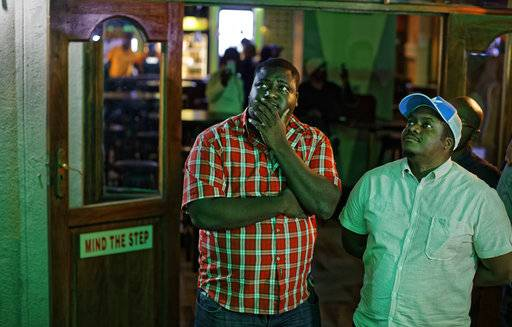 Disappointed Zimbabweans watch a televised address to the nation by President Robert Mugabe at a bar in downtown Harare, Zimbabwe Sunday, Nov. 19, 2017. Zimbabwe's President Robert Mugabe has baffled the country by ending his address on national television without announcing his resignation.