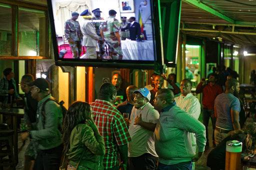 Disappointed Zimbabweans discuss their shock as the credits roll at the end of a televised address to the nation by President Robert Mugabe at a bar in downtown Harare, Zimbabwe Sunday, Nov. 19, 2017. Zimbabwe's President Robert Mugabe has baffled the country by ending his address on national television without announcing his resignation.