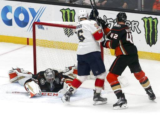 Anaheim Ducks goalie John Gibson (36) blocks a shot on goal as defenseman Josh Manson (42) and Florida Panthers center Aleksander Barkov (13) in the second period of an NHL hockey game in Anaheim, Calif., Sunday, Nov. 19, 2017.
