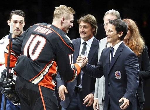 Anaheim Ducks right winger Corey Perry (10) shakes congratulates NHL Hall of Fame inductees and former Anaheim Ducks Paul Kariya, right, and Teemu Selanne, center, after a ceremonial puck drop as the pair are honored before a hockey game between the Ducks and the Florida Panthers in Anaheim, Calif., Sunday, Nov. 11, 2017.