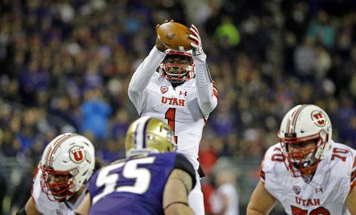 Utah quarterback Tyler Huntley reaches for a high snap during the first half of an NCAA college football game against Washington on Saturday, Nov. 18, 2017, in Seattle.
