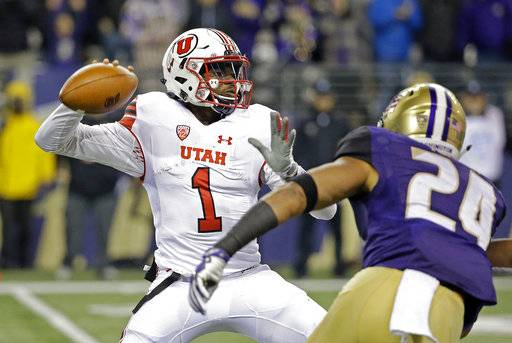 Utah quarterback Tyler Huntley (1) readies a pass as Washington defender Ezekiel Turner moves in during the first half of an NCAA college football game Saturday, Nov. 18, 2017, in Seattle.
