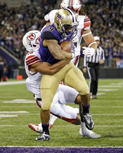 Washington's Myles Gaskin pulls a Utah defender with him as he scores on a 9-yard run during the first half of an NCAA college football game Saturday, Nov. 18, 2017, in Seattle.