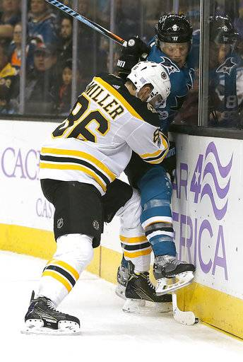 San Jose Sharks center Joe Pavelski (8) is checked into the boards by Boston Bruins defenseman Kevan Miller (86) during the second period of an NHL hockey game Saturday, Nov. 18, 2017, in San Jose, Calif.