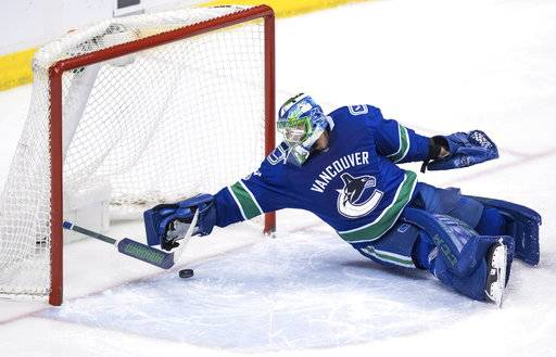 Vancouver Canucks' goalie Anders Nilsson, of Sweden, loses his stick as he prevents the puck from entering the net during the second period of an NHL hockey game agains the St. Louis Blues on Saturday, Nov. 18, 2017, in Vancouver, British Columbia. (Darryl Dyck/The Canadian Press via AP)