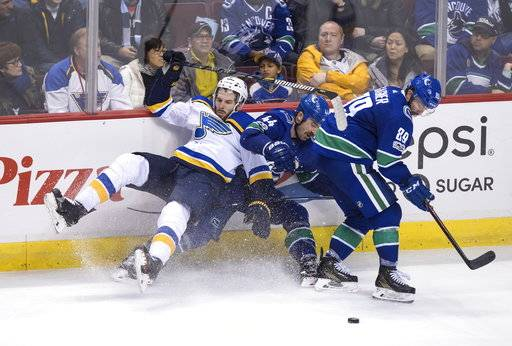 St. Louis Blues' Joel Edmundson, left, and Vancouver Canucks' Erik Gudbranson (44) collide behind Sam Gagner (89) during the third period of an NHL hockey game in Vancouver, B.C., on Saturday November 18, 2017. THE CANADIAN PRESS/Darryl Dyck/The Canadian Press via AP)