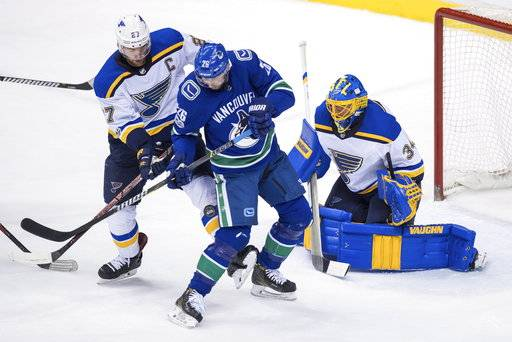 Vancouver Canucks' Thomas Vanek (26), of Austria, is struck by the puck and checked by St. Louis Blues' Alex Pietrangelo (27) in front of goalie Jake Allen during the second period of an NHL hockey game Saturday, Nov. 18, 2017, in Vancouver, British Columbia. (Darryl Dyck/The Canadian Press via AP)