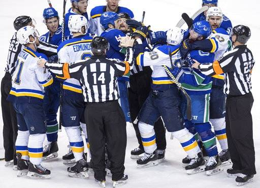 St. Louis Blues' Alexander Steen (20) gets into a scuffle with Vancouver Canucks' Erik Gudbranson (44) and Thomas Vanek (26), of Austria, during the second period of an NHL hockey game Saturday, Nov. 18, 2017, in Vancouver, British Columbia. (Darryl Dyck/The Canadian Press via AP)