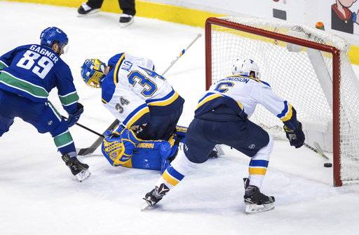 Vancouver Canucks' Sam Gagner (89) watches as a shot by Sven Baertschi, not seen, gets past St. Louis Blues goalie Jake Allen for a goal while Joel Edmundson (6) reaches for the puck during the second period of an NHL hockey game Saturday, Nov. 18, 2017, in Vancouver, British Columbia. (Darryl Dyck/The Canadian Press via AP)