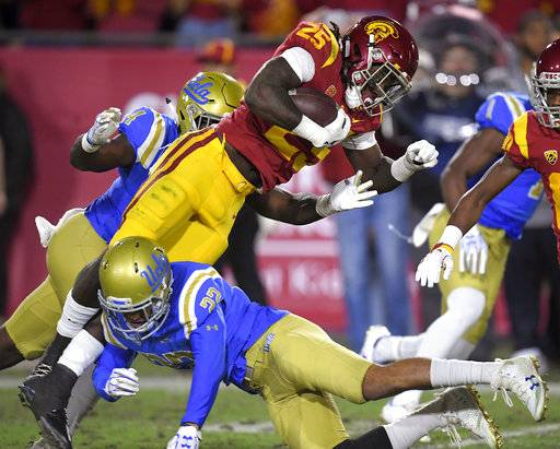 Southern California running back Ronald Jones II, top, is tackled by UCLA defensive back Nate Meadors during the first half of an NCAA college football game, Saturday, Nov. 18, 2017, in Los Angeles.