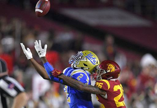 UCLA wide receiver Jordan Lasley, left, makes a catch while under pressure from Southern California cornerback Jack Jones during the first half of an NCAA college football game Saturday, Nov. 18, 2017, in Los Angeles.