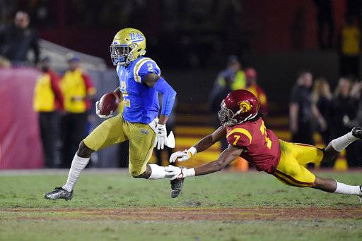 UCLA wide receiver Jordan Lasley, left, escapes a tackle by Southern California safety Marvell Tell III during the first half of an NCAA college football game, Saturday, Nov. 18, 2017, in Los Angeles.