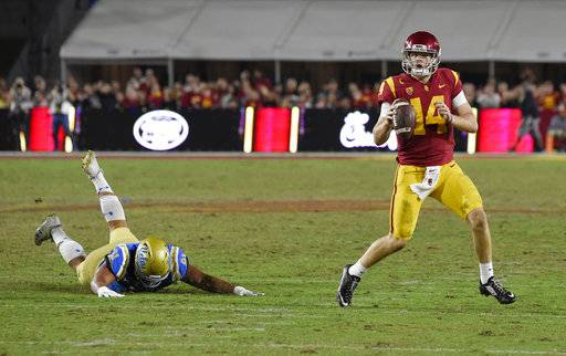 Southern California quarterback Sam Darnold, right, scrambles with the ball as UCLA defensive lineman Jacob Tuioti-Mariner falls during the first half of an NCAA college football game, Saturday, Nov. 18, 2017, in Los Angeles.