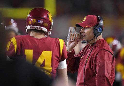 Southern California head coach Clay Helton, right, talks with quarterback Sam Darnold during the first half of an NCAA college football game against UCLA, Saturday, Nov. 18, 2017, in Los Angeles.