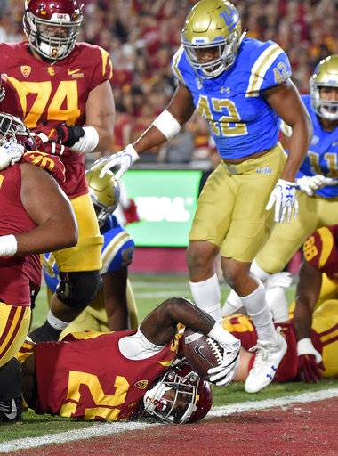 Southern California running back Ronald Jones II, below, gets in for a touchdown as center Nico Falah, upper left, and UCLA linebacker Kenny Young watch during the first half of an NCAA college football game, Saturday, Nov. 18, 2017, in Los Angeles.
