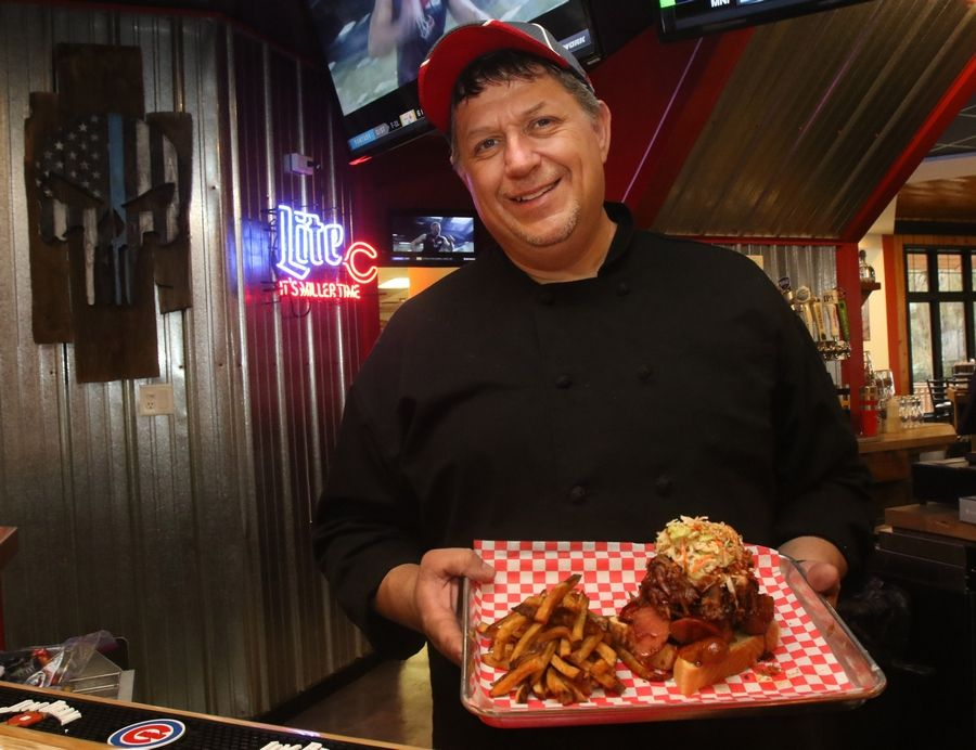 Executive chef Dean Dassler shows off the hot link pulled pork stacker at BBQ'd Productions Bar & Grill in Lake Zurich.