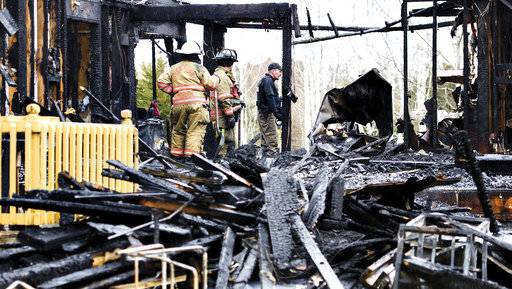 Fire investigators work at the scene of a fatal fire Tuesday, Nov. 21, 2017 outside of Dixon, IL.  Authorities say two adults and four children died in the early morning house fire. (Alex T. Paschal/Sauk Valley Media via AP)