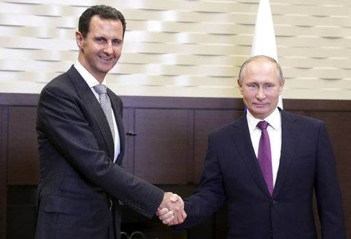 In this image made from Monday, Nov. 20, 2017, video, Russian President Vladimir Putin, center right, stands with Syria's President Bashar Assad in Sochi, Russia. Russian state television reported that Putin met with Assad and held bilateral talks on Monday and met with Russian military chiefs. It was the second time Assad has traveled to Russia to meet with Putin in the course of the country's six-year civil war. (RU-24 via AP Video)