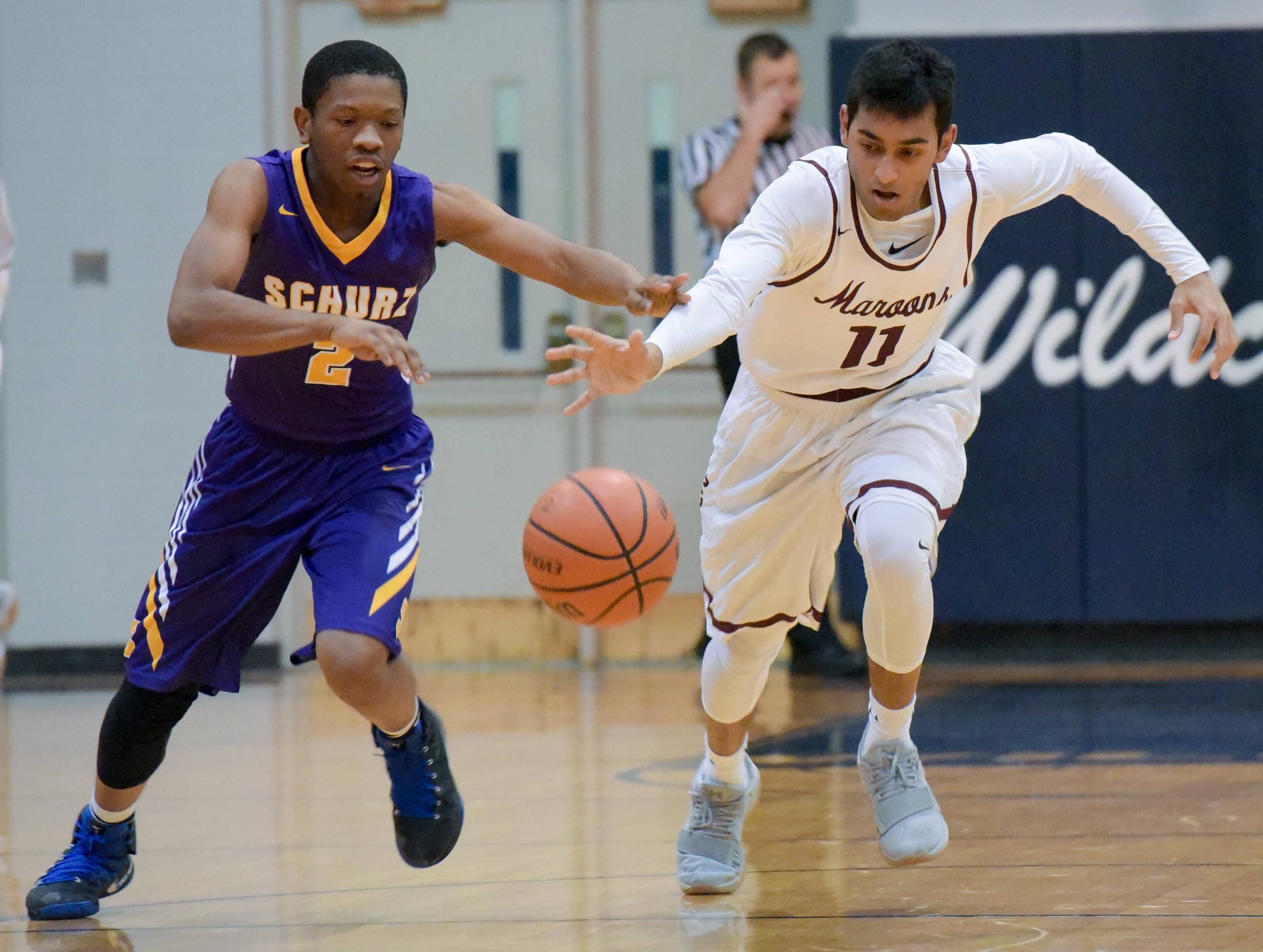 Schurz's Antwon Brooks and Elgin's Dan Toolsie scramble for a loose ball during varsity boys basketball in West Chicago Wednesday.