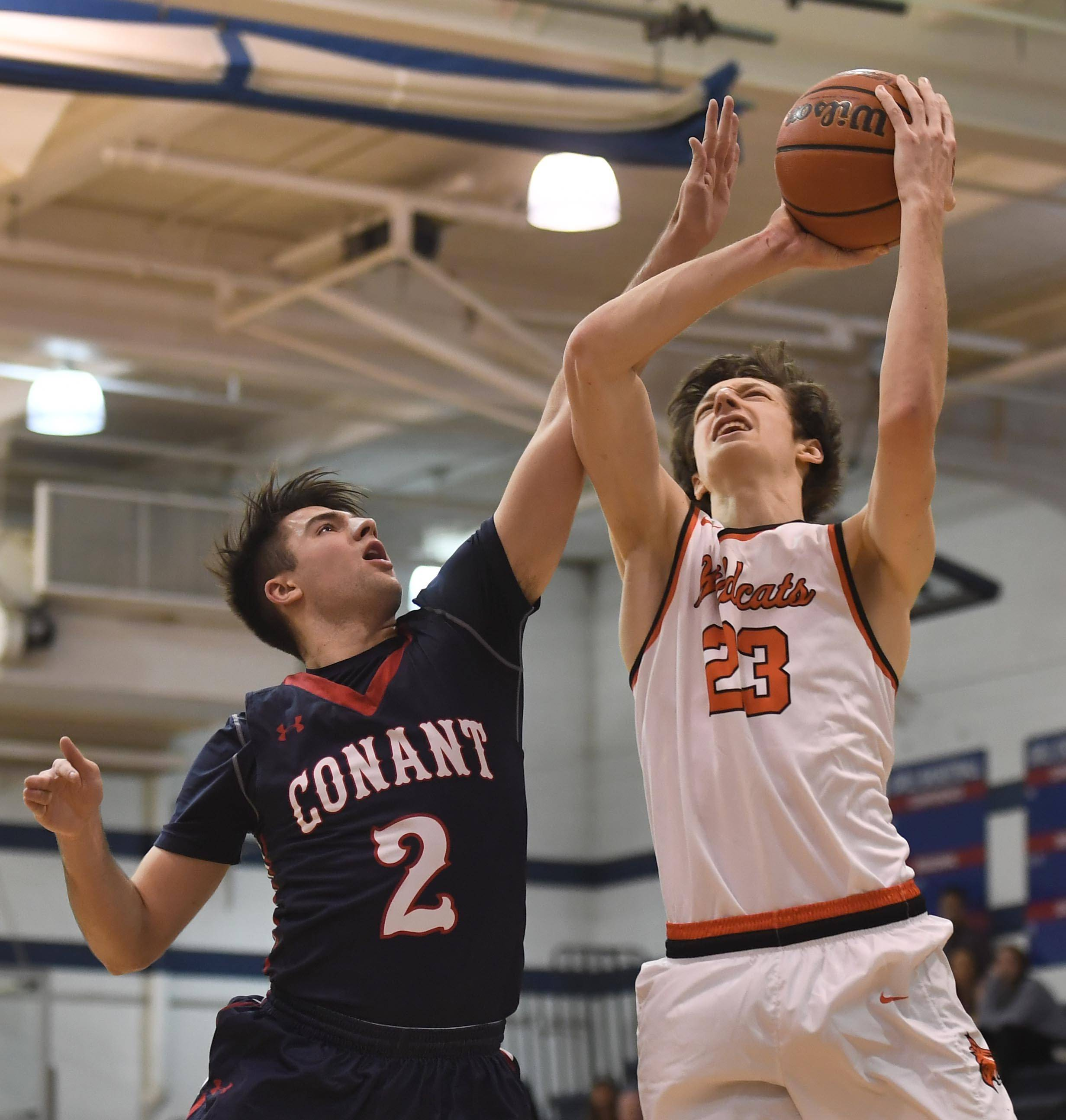 Libertyville's Drew Peterson, right, gets fouled by Conant's Ben Schols during the St. Viator Thankgiving Tournament play in Arlington Heights on Wednesday.