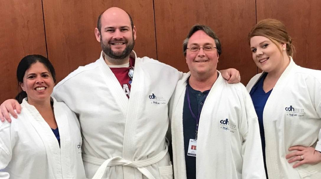 On his final day of proton therapy treatment at the Northwestern Medicine Chicago Proton Center, Scott McLintock (second from left) and staff members Bridget Cook, Jarrod Walters, and  Danielle Bobor wear Chicago Proton Center robes.Northwestern Medicine