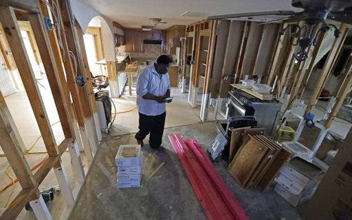 In this Nov. 17, 2017 photo, George Dorsey walks through his hurricane-damaged home in Houston. He usually hosts a large Thanksgiving dinner for family but is making other arrangements this year as he continues to recover from Hurricane Harvey. (AP Photo/David J. Phillip)