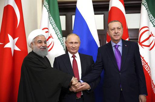 Turkey's President Recep Tayyip Erdogan, right, Russia's President Vladimir Putin, center, and Iran's President Hassan Rouhani pose for the media members in Sochi, Russia, Wednesday, Nov. 22. 2017. Leaders of Turkey and Iran have arrived in Russia's Sochi for the much-anticipated talks with President Vladimir Putin that are expected to focus on a political settlement for post-war Syria. (Kayhan Ozer/Pool via AP)