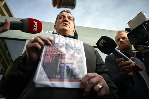Fikret Alic, holds holds a copy of a magazine bearing his image, after the verdict which the Yugoslav War Crimes Tribunal, ICTY, handed down in the genocide trial against former Bosnian Serb military chief Ratko Mladic, in The Hague, Netherlands, Wednesday Nov. 22, 2017. Alic, a Bosnian man who became a figurehead for the suffering of Bosnians during the war when he was photographed as an emaciated prisoner behind the wire of a Bosnian Serb prison camp, was among those who watched the hearing. A U.N. court has convicted former Bosnian Serb military chief Gen. Ratko Mladic of genocide and crimes against humanity and sentenced him to life in prison for atrocities perpetrated during Bosnia's 1992-1995 war. (AP Photo/Phil Nijhuis)